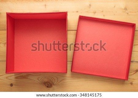 Empty red box with cover on a wooden background - stock photo