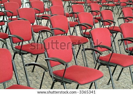 Empty red chairs in outdoor auditorium or conference hall.