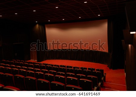 Empty red cinema with white screen and seats. Side view