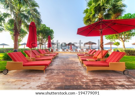 Empty red deckchairs at the sea in Abu Dhabi - stock photo