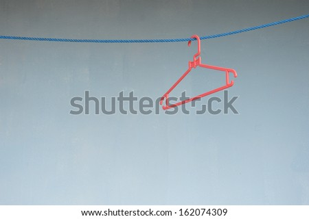 empty red hangers on blue line against blue wall - stock photo