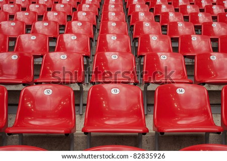 Empty red plastic seats in a stadium. - stock photo