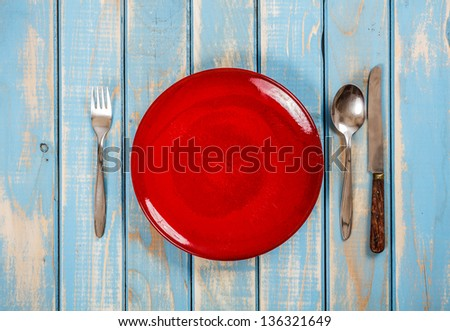 Empty red plate on blue wooden table with knife, spoon and fork - stock photo