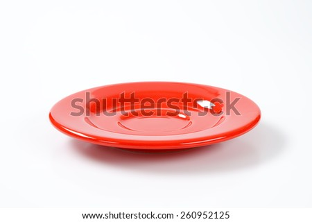 empty red saucer on white plate - stock photo