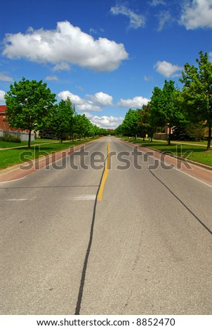 Empty residential street in suburban neighborhood lined with trees - stock photo