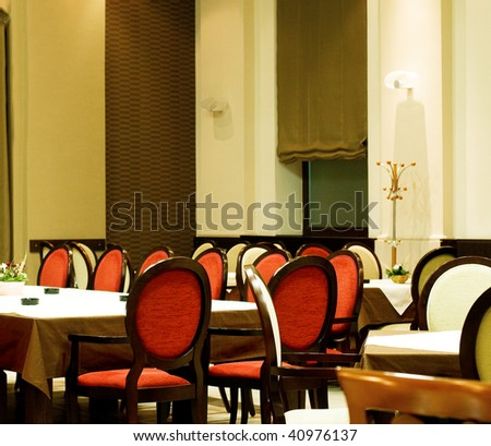 Empty restaurant at night light, tables ready for dinner - stock photo
