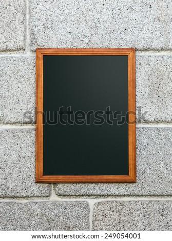 Empty Restaurant Blackboard in a Stone Wall - stock photo
