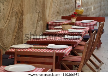 Empty restaurant chairs and tables in an old street in Montenegro - stock photo