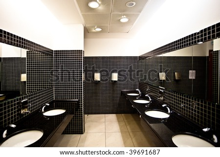Empty restroom interior in brown and white with washstands, dryers and mirrors - stock photo