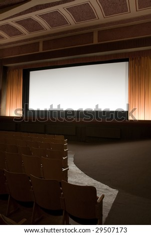 Empty retro cinema auditorium in cubism style with line of chairs and projection screen. Ready for adding your own picture. - stock photo