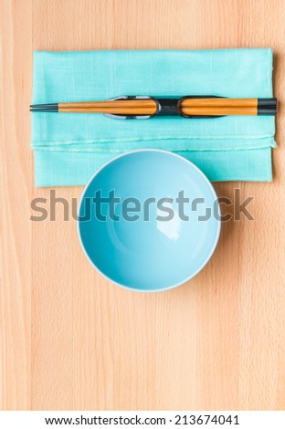Empty rice bowl with bamboo chopsticks on wooden table. - stock photo