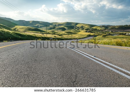 Empty road across green hills - stock photo