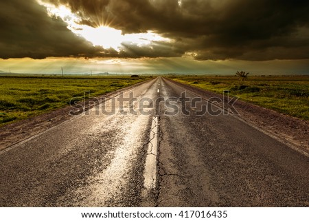 Empty road after rain vanishing into the sunset - stock photo