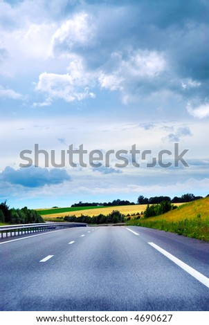 Empty road among fields with blue cloudy sky - stock photo