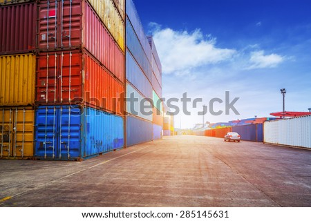 Empty road and containers in harbor at sunset - stock photo
