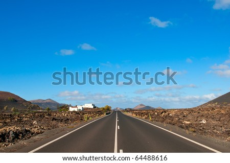 Empty road between rocks in the Lanzarote island, Canary islands, Spain in summer sunny day - stock photo