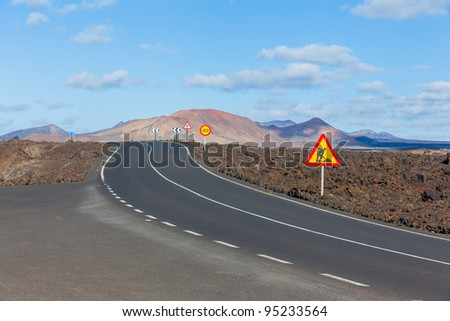 Empty road crossing the lava in the mountain, Lanzarote, Canary islands, Spain - stock photo