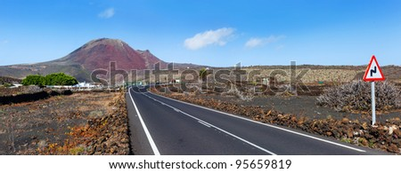 Empty road crossing the lava in the mountain, volcano backround. Panorama. Lanzarote, Canary islands, Spain - stock photo