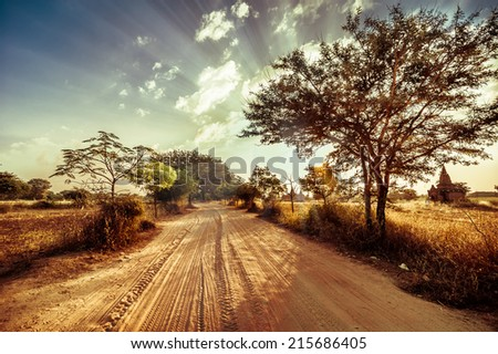 Empty road going through rural landscape under sunset sky with sun beams. Dry season in southeast asia, Myanmar (Burma). Nature background in vintage style - stock photo