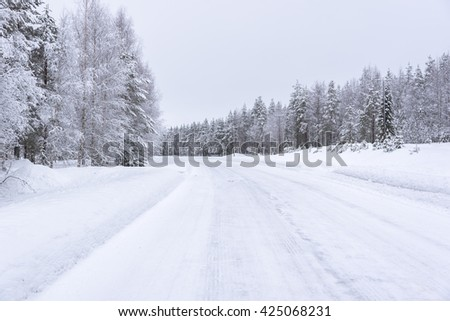 Empty road in Finland covered in snow on winter cloudy day