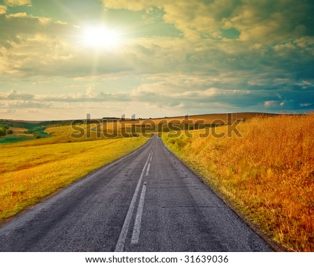 Empty road in the sunset - stock photo