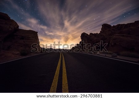 Empty Road leading towards the  rising moon  Valley of Fire State Park, Overton Nevada  - stock photo