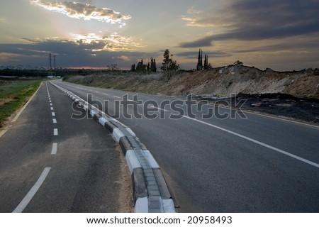 empty road near the city at sunset - stock photo