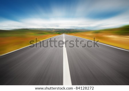 Empty road on the countryside with a speedy motion blur effect - stock photo