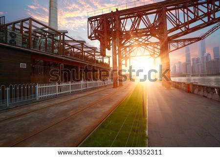 Empty road surface floor and pier of iron tower with modern city landmark architecture backgrounds of sunset in Guangzhou China - stock photo