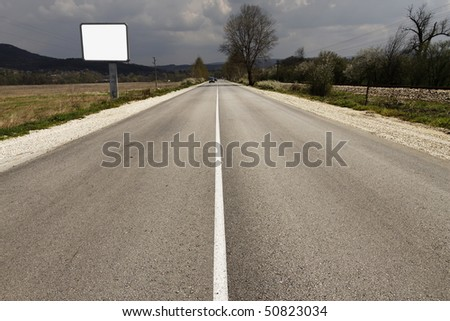 empty road through fields with blank billboard beside - stock photo