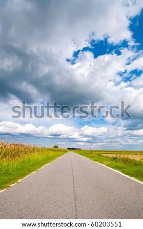 Empty road through the plains - stock photo