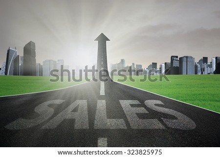 Empty road with a sales text turning into arrow upward to the sky with bright sunlight - stock photo