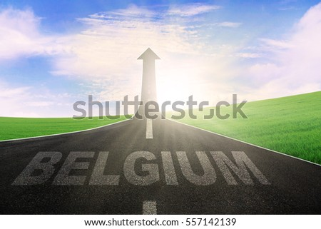 Empty road with word of Belgium and arrow upward at the end of a road