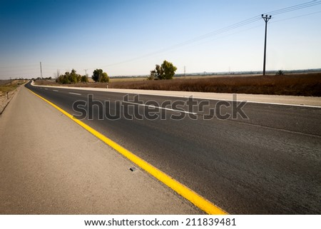 Empty road with yellow and white stripes under blue sky - stock photo