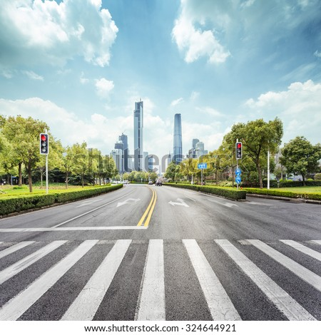 empty road with zebra crossing and skyscrapers in modern city - stock photo
