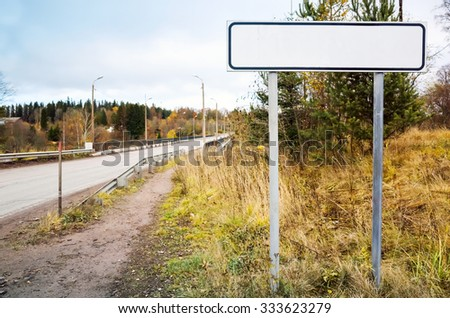 Empty roadsign stands near rural European highway - stock photo