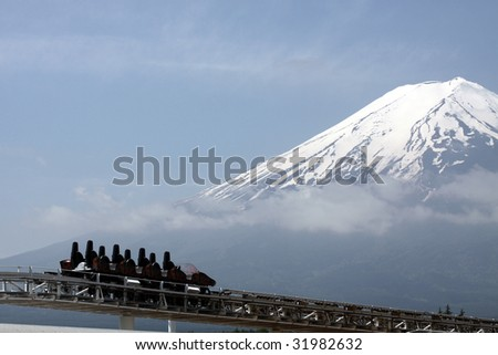 Empty rollercoaster car in front of clouded Mt. Fuji - stock photo