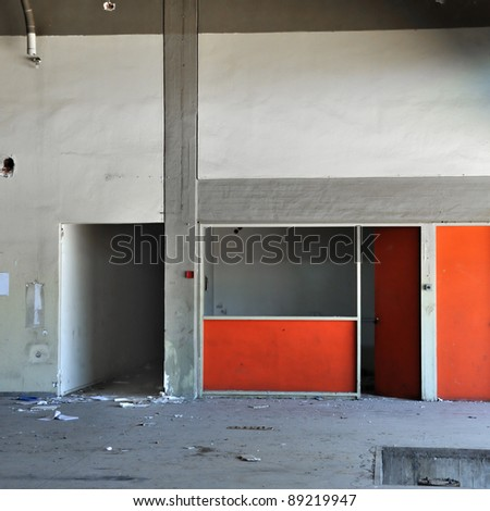Empty room concrete wall and dark hallway in abandoned factory interior. - stock photo