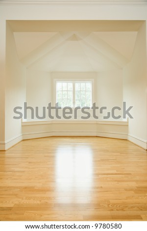 Empty room in house with sunlight coming through window on hardwood floors. - stock photo