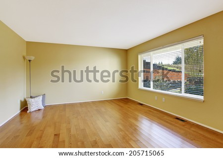 Empty room in soft ivory with new hardwood floor and window. Decorated with lamp and pillows