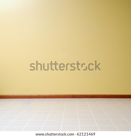 Empty room with a linoleum floor with a yellow painted wall