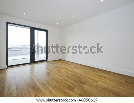 empty room with balcony access and hard wood floor - stock photo