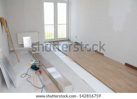 Empty room with laminate floor installation - stock photo