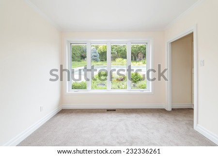 Empty room with large window looking on summer backyard and residential pool - stock photo