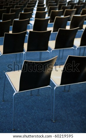 Empty room with many chairs on blue carpet - stock photo