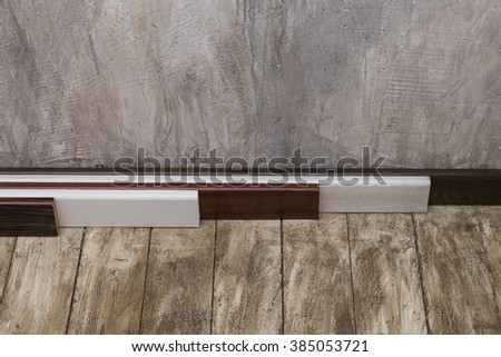 Empty room with old wood floor and rough plaster walls. Wooden Skirting boards - stock photo