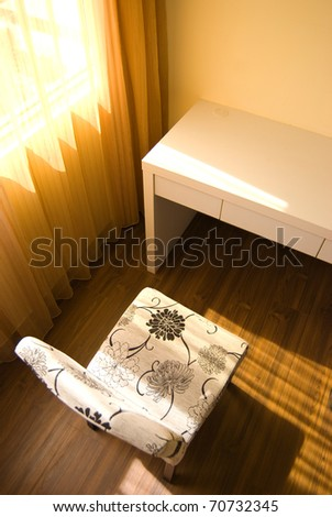 Empty room with single table and chair under sunlight - stock photo