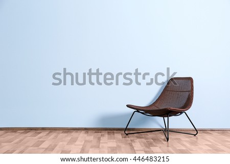 Empty room with wicker chair  on blue wall background - stock photo