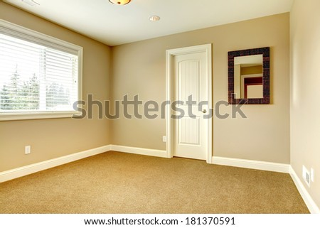 Empty room with window, carpet floor and mirror