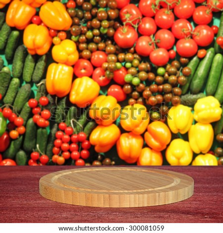 Empty round cutting board on wooden table.In the background blurred lot of ripe vegetables - stock photo